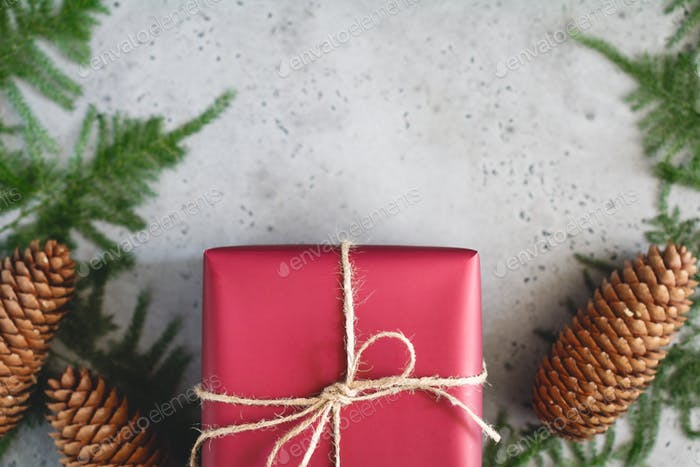 Red Christmas gift box is tied of twine among winter decoration. Flat lay, top view.