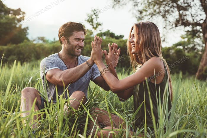 Happy young couple enjoying a day in meadow