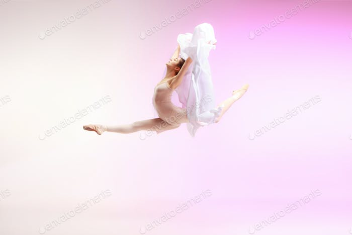 Ballerina. Young graceful female ballet dancer dancing over pink studio. Beauty of classic ballet.