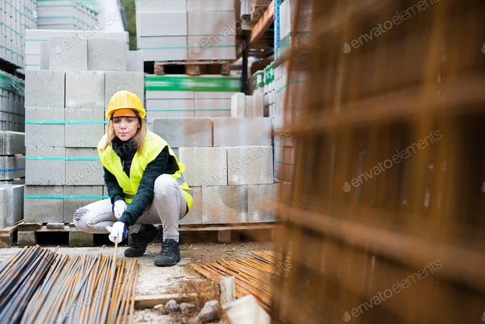 Junge Arbeiterin in einem Industriegebiet.