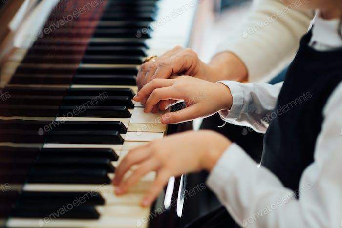 erfahrene Klaviermeister Hand hilft dem Schüler
