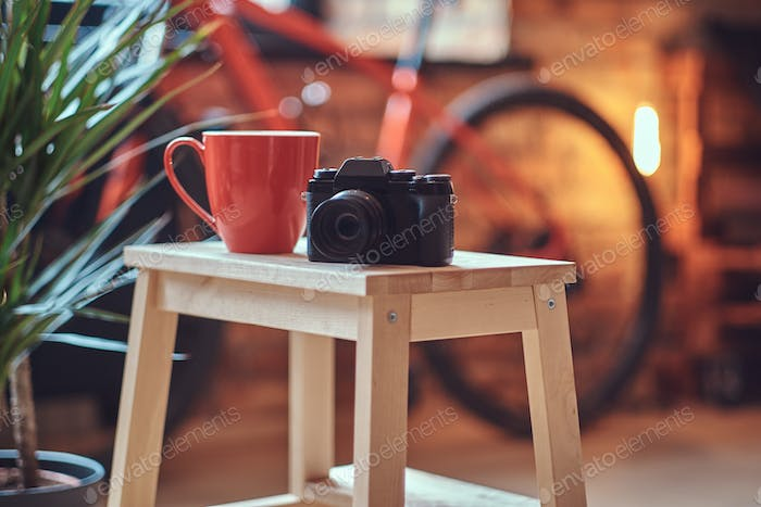 Close-up image of a red cup and a camera on a wooden stool on a room with a loft interior.