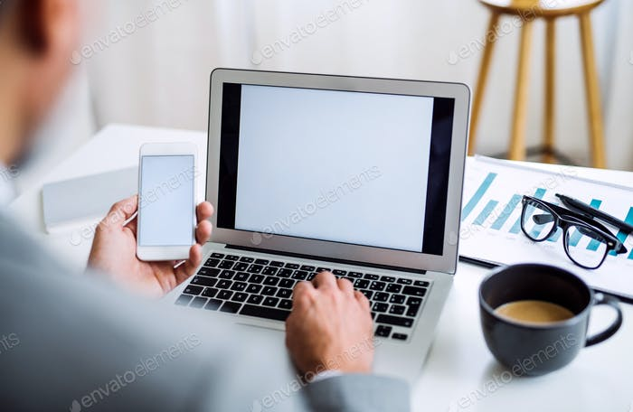 A midsection of businessman with smartphone and laptop sitting at the table, working.