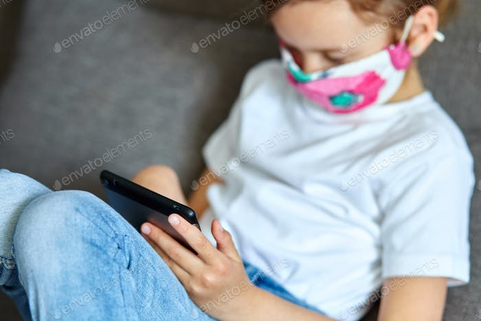 Little girl in protection mask using, play tablet or learning with video call online