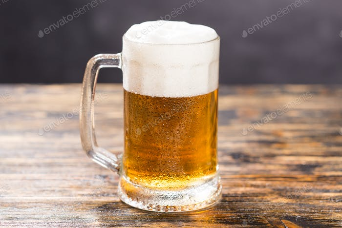 Mug of cold pale beer placed on a rustic wooden table with copy space
