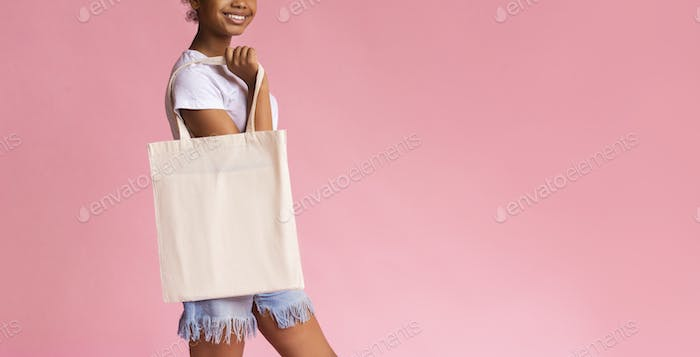 Smiling African American girl holding blank cotton bag