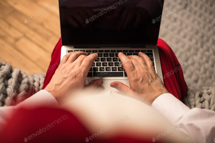 Hands of Santa Claus typing on laptop