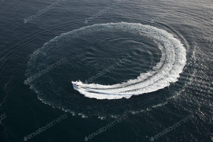 Small yacht making a circle in the water