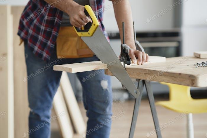 Man cutting block of wood using hand saw