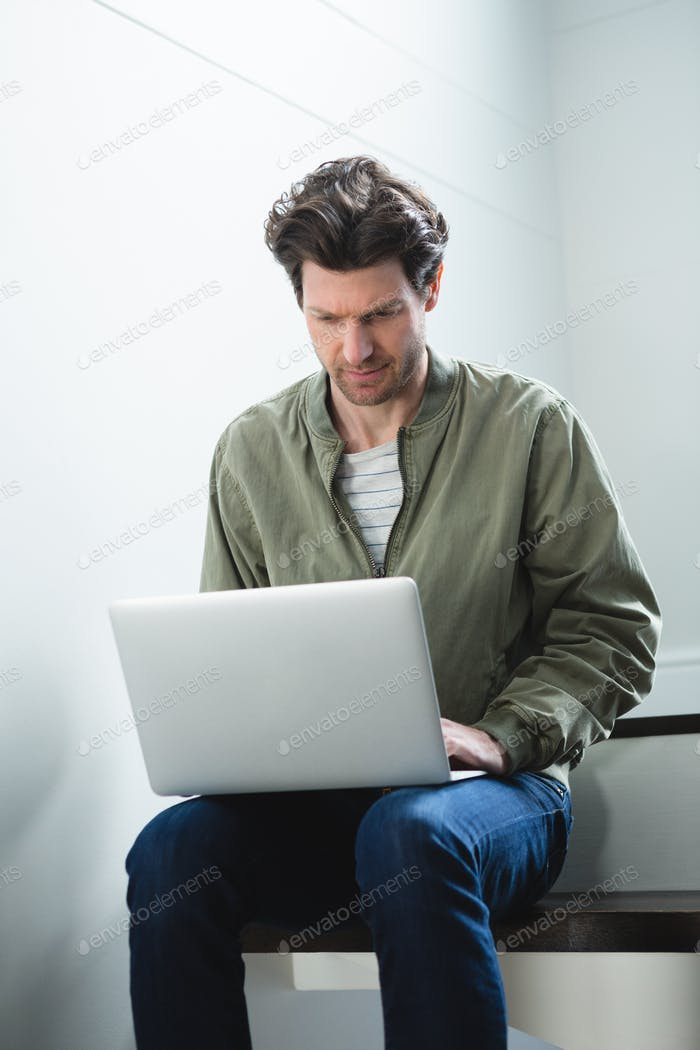 Man using laptop in stairs at home