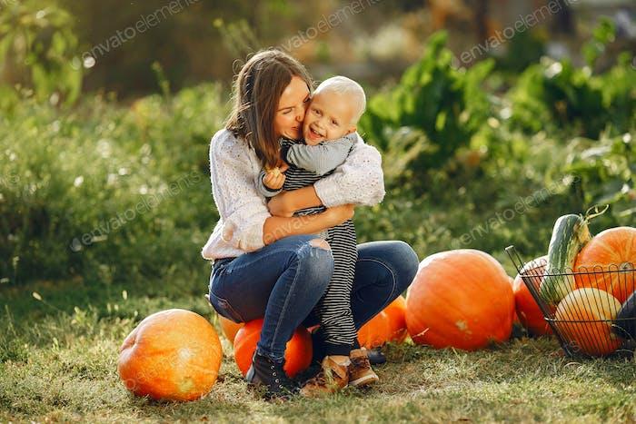 Mutter und Sohn sitzen auf einem Garten in der Nähe von vielen Kürbissen