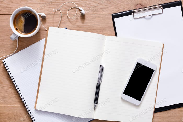 Office supplies and mobile phone at wood background