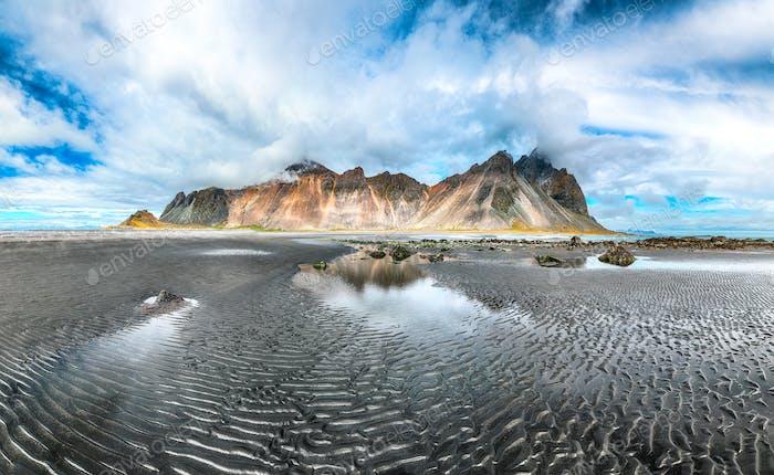 Dramatisch sonniger Tag und wunderschöner, gewellter schwarzer Sandstrand am Stokksnes-Kap in Island.