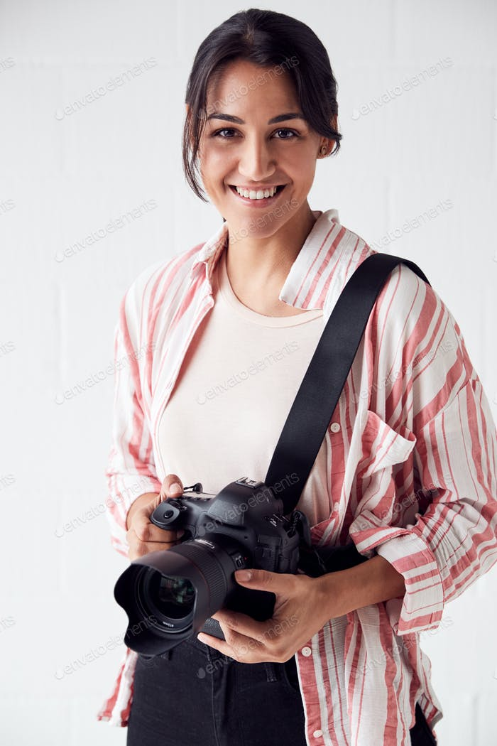 Portrait Of Smiling Female Photographer With Camera Against White Studio Wall