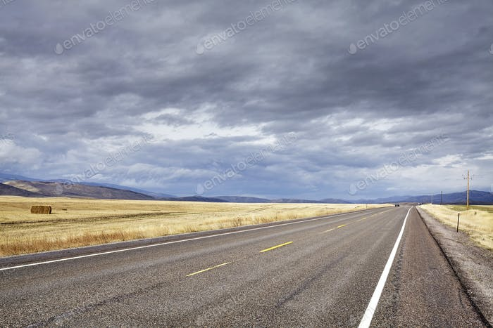 Countryside road with rainy clouds.