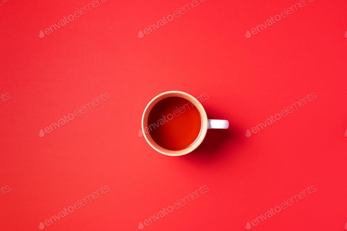 Cup of tea on red background. Top view. Copy space. Banner. Autumn or winter season concept