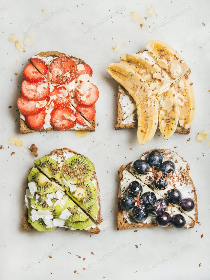 Healthy breakfast toasts with fruit, nuts and cream cheese