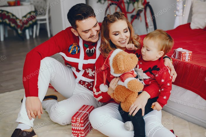 Cute young family sitting at home on a bed
