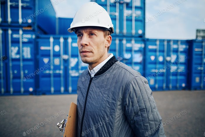 Dock foreman standing alone in a commercial shipping yard