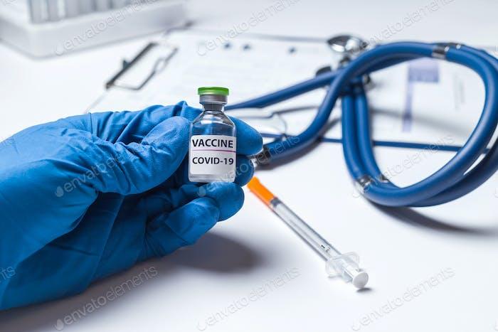 Hand des Arztes, Wissenschaftlers oder der Krankenschwestern in blauen Handschuhen mit einer Durchstechflasche mit Coronavirus-Impf