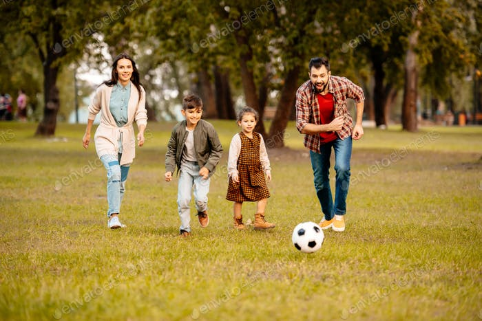 Family with two children playing football together in an autumn park