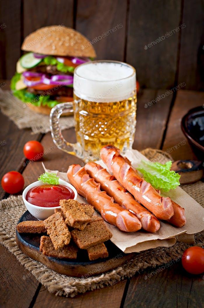 Saucisses grillées, craquelins et bière sur fond en bois dans un style rustique