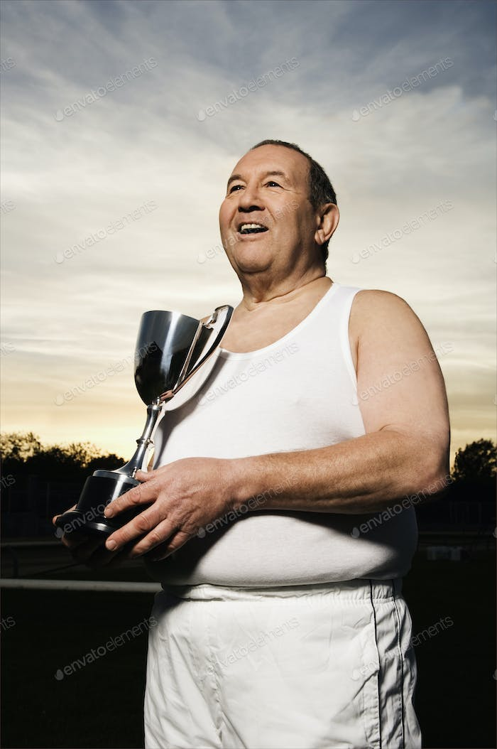 Smiling elderly men in sportswear, holding a silver trophy.