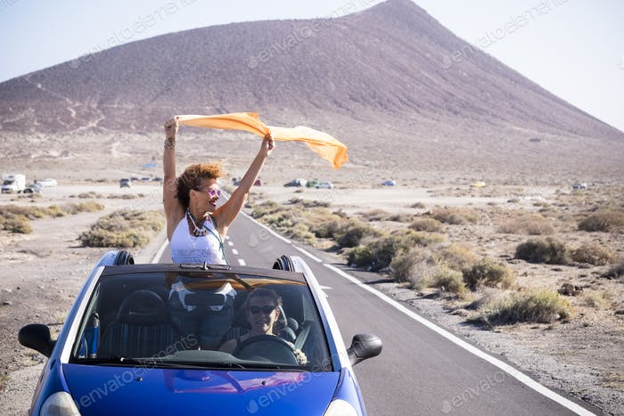 Couple of happy woman travel together with convertible car on a long road having fun
