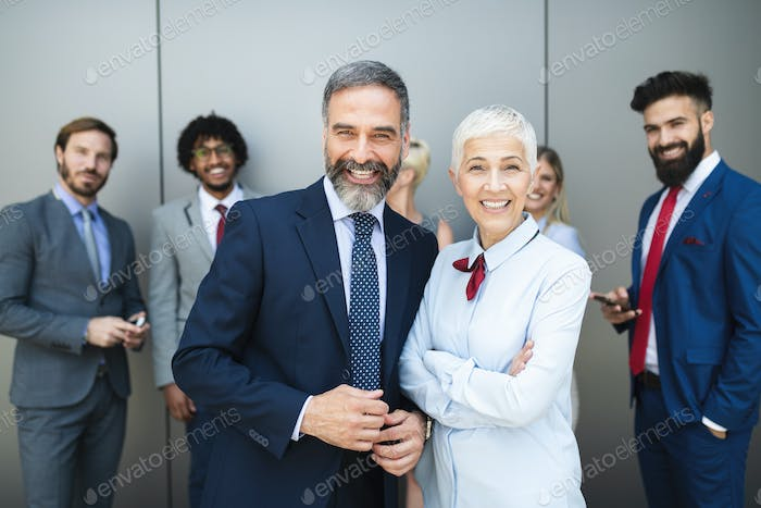 Portrait of businesspeople standing with arms crossed in office