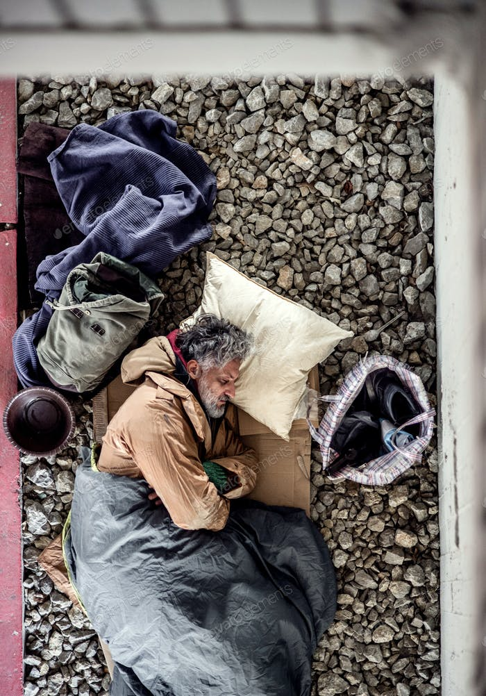 A top view of homeless beggar man lying on the ground outdoors in city, sleeping.
