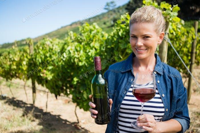 Portrait of female vintner examining wine in vineyard