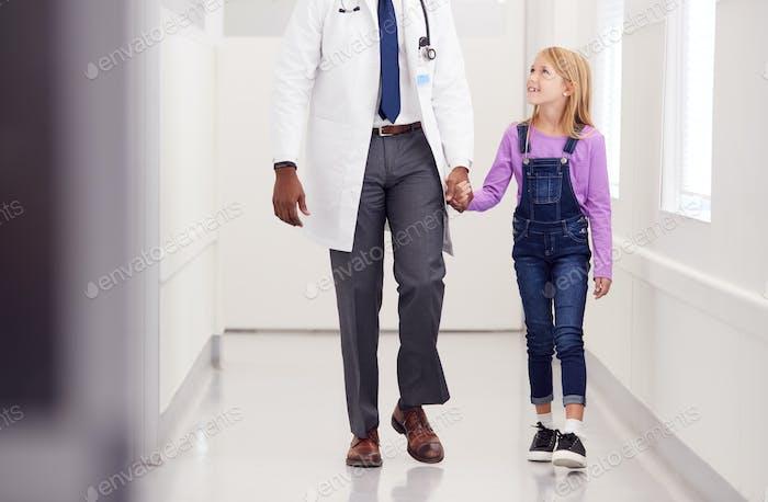Nahaufnahme von männlichen pädiatrischen Arzt zu Fuß entlang Krankenhaus Korridor halten Hände mit Mädchen Patienten