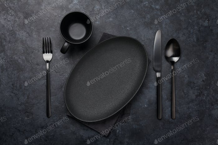 Empty plate, fork, spoon and knife