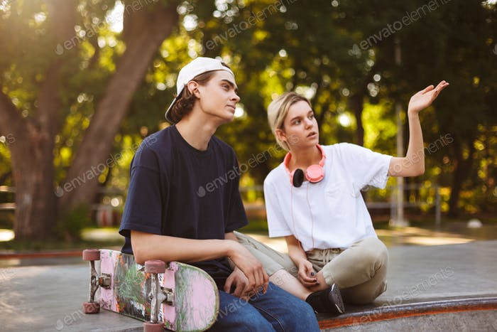 Pretty girl with headphones and young guy with skateboard though