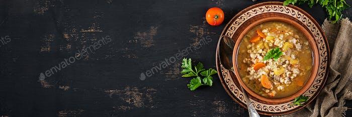 Gerstensuppe mit Karotten, Tomaten, Sellerie und Fleisch auf einem dunklen Rücken