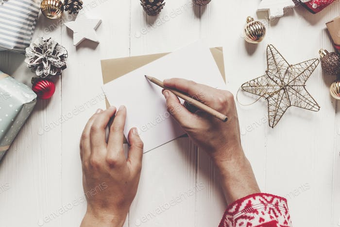 kid hands holding pencil and making wish list and paper with christmas decorations