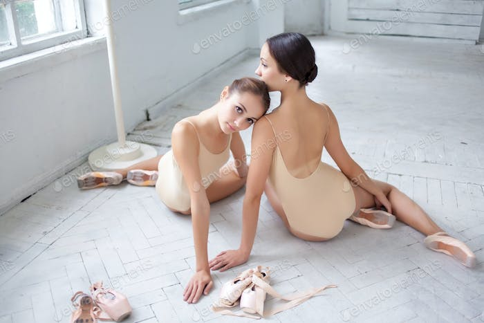 The two classic ballet dancers posing on white wooden floor