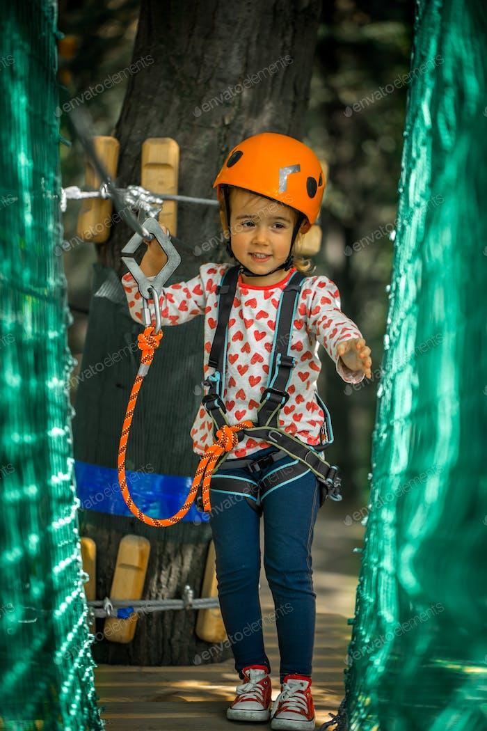 sports happy kid climbs through the ropes