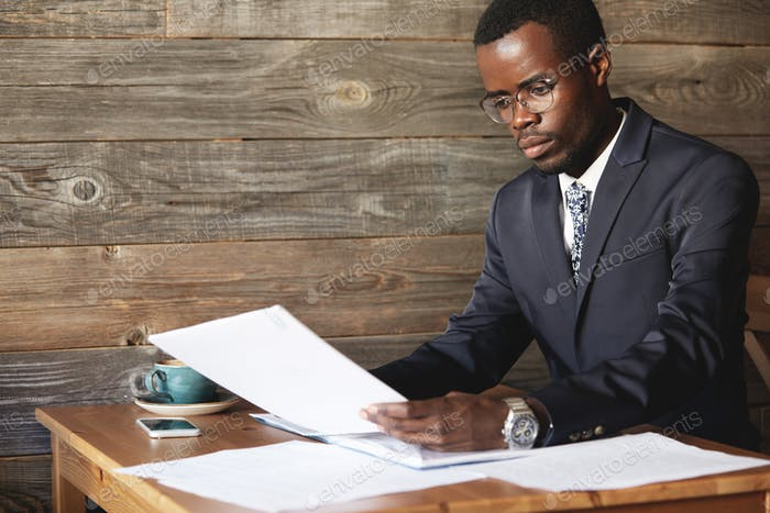 Young African accountant wearing formal wear, holding documents, dealing with paperwork, administrat