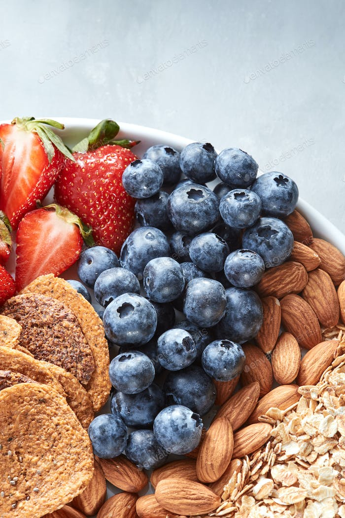 Fresh ripe fruits, blueberry, almond nuts, oat flakes, crisps on a plate on a gray background
