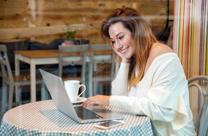 Business woman working with laptop and mobile phone at cafe, freelance concept
