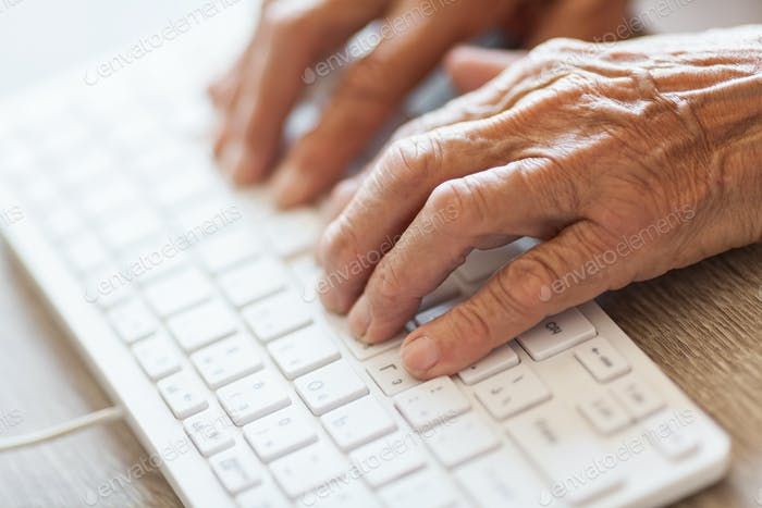 Elderly woman typing on a keyboard