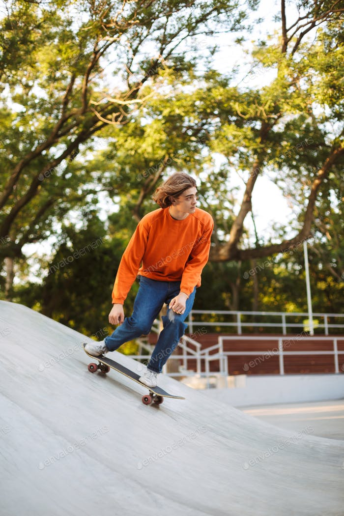 Young guy in orange pullover skateboarding and practicing stunts