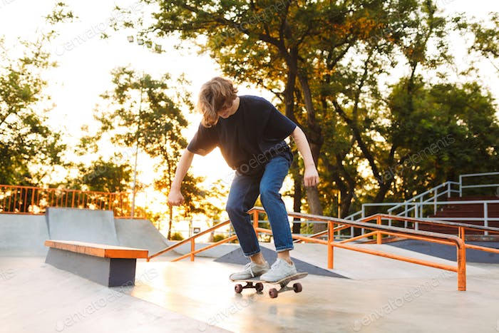 Young cool skater in black T-shirt and jeans riding on skateskat