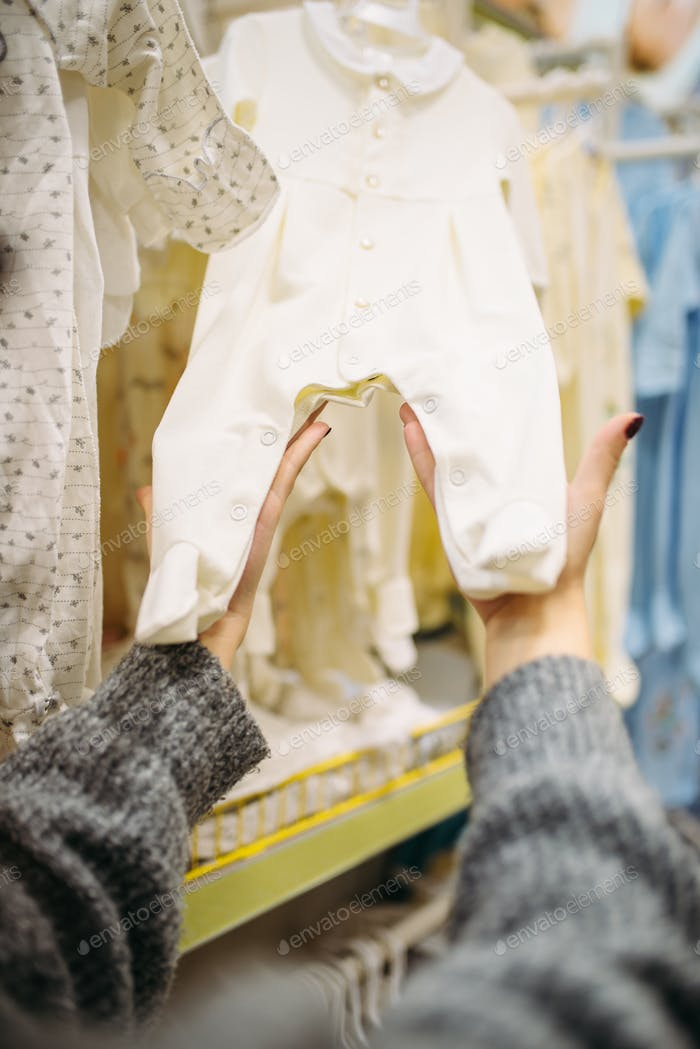 Female person chooses baby clothes in the store