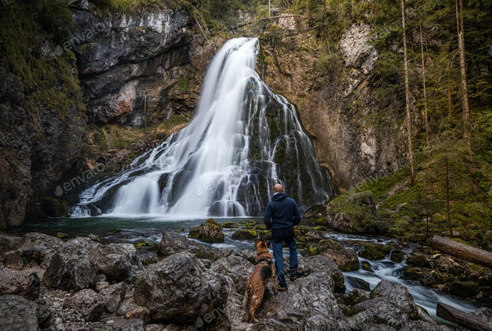 Adventure Man with Dog Hiking at Gollinger Waterfall in Austria