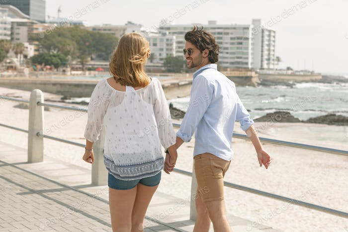 Caucasian couple walking hand in hand on the promenade at the seaside on a sunny day