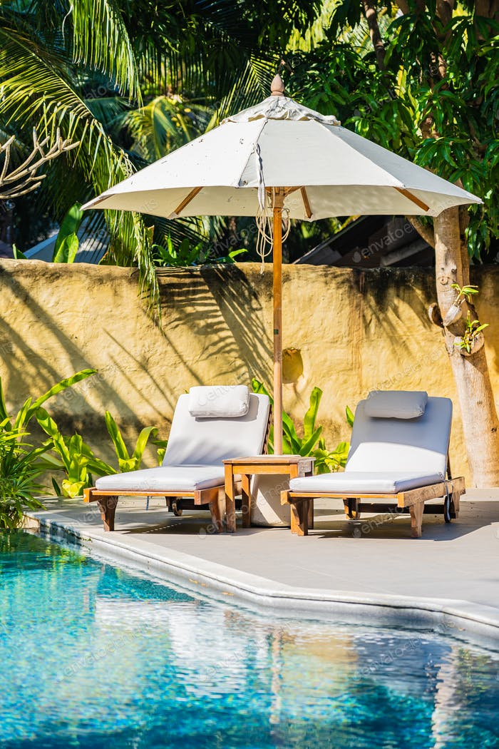 Umbrella and chair around outdoor swimming pool