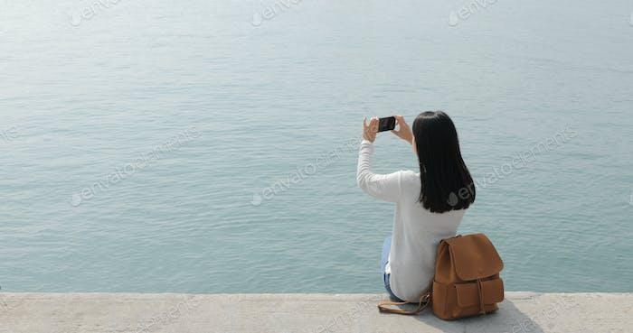 Женщина делает фото на мобильный телефон с морской пейзаж