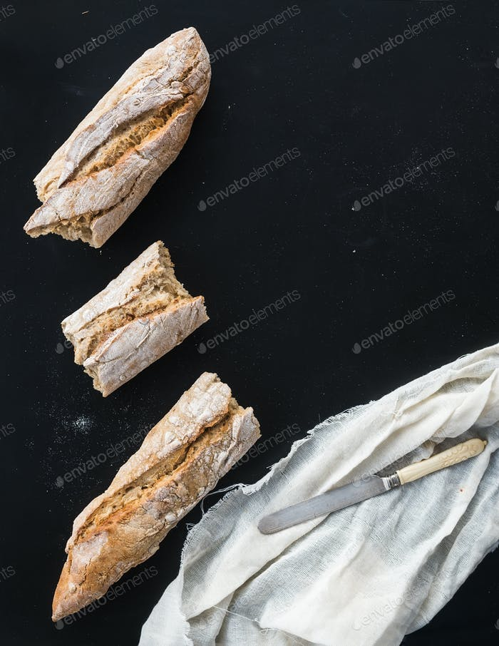 French baguette broken into pieces, white kitchen towel and vint